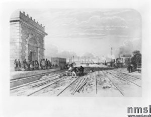 A lithograph of Crewe station, Cheshire, 1848. This was one of fifteen scenes of the London & North Western Railway produced by the artist and lithographer A F Tait, and published by Bradshaw and Blacklock in Manchester. Before the coming of the railways Crewe was a small hamlet. However, in the 1830s it became the junction of the Chester & Crewe Railway, Manchester & Birmingham Railway, and the Grand Junction Railway. The hamlet quickly expanded and the surrounding land was used as the site of its locomotive and carriage works.