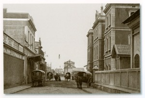 """Façana de l'Estació Nova de Mataró amb làmpades d'arc voltaic penjades en el centre del carrer, vers 1905. Cablejat aeri conegut popularment com """"fils de guitarra"""". Vers l'any 1905."""